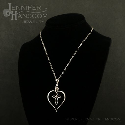 Small silver cable chain necklace on form with pendant