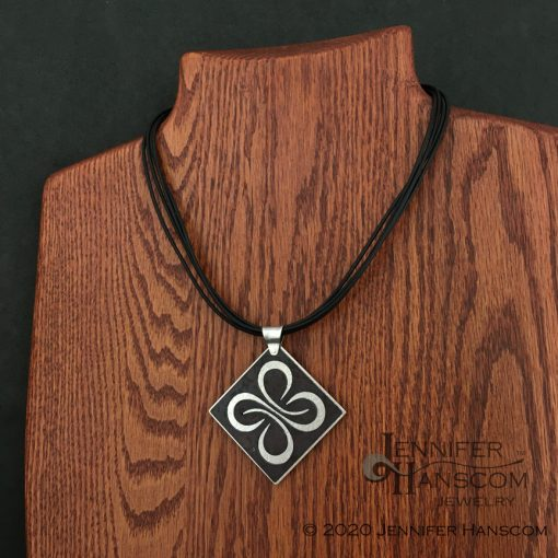 Multi-strand leather necklace on form with pendant