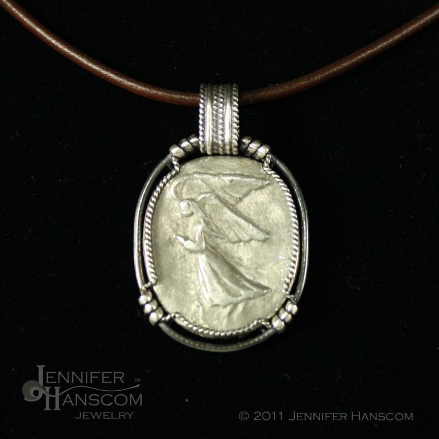 Angel Coin wrapped in silver wire with a masculine feel and wide bail